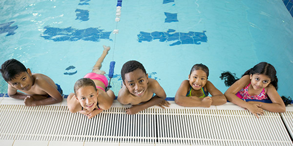 Five children on the edge of the pool smiling