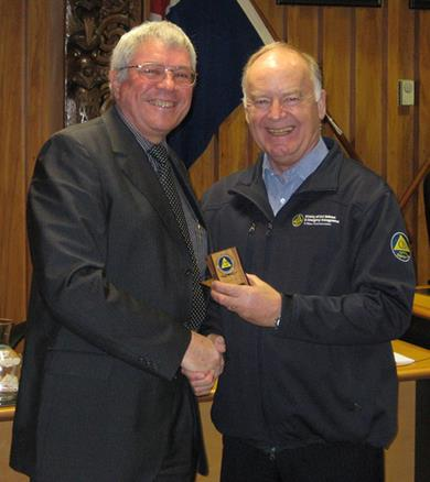 Rian van Schalkwyk, left, receives his long service award from Director CDEM John Hamilton.