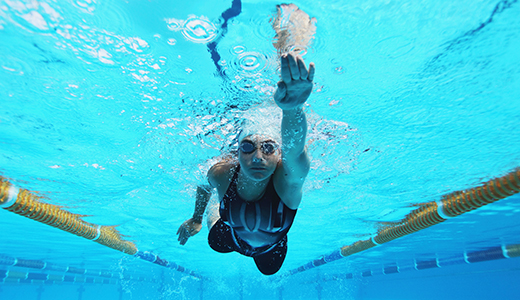 A girl swimming under water in a pool