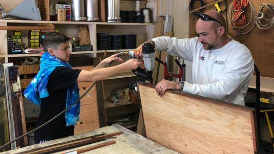 Photo of a man and his son working with power tools