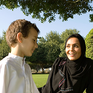 Mother wearing hijab and son sitting in a park
