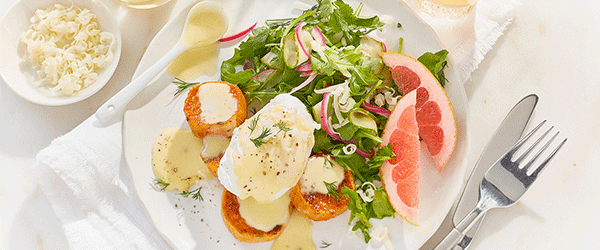 Eggs benedict with cheese and hollandaise sauce and slices of grapefruit on the side.