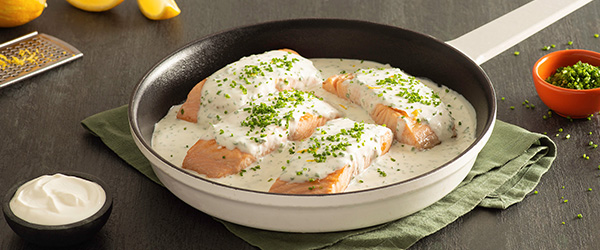 Photo of four fresh salmon filets baked in a pan with a lemon cream sauce.
