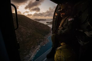 Leading Seaman Aircrewman Michael Sales surveys the coast from HMAS Parramatta's embarked MH-60R helicopter over the Whitsunday Islands. Defence
