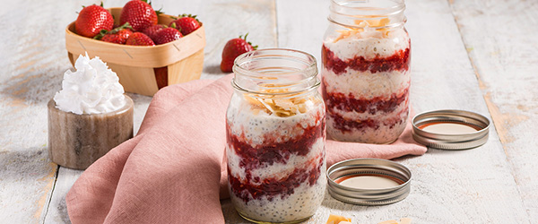 Photo of jars of fruit and oats with whipped cream and strawberries in the background.