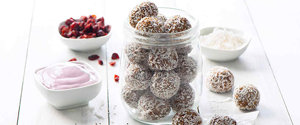Berry coconut protein bliss balls in a glass gar on a wooden table with toppings.