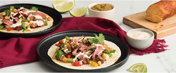 Photo of Two plates of steak fajitas with vegetables, sour cream and chipotle cheese.