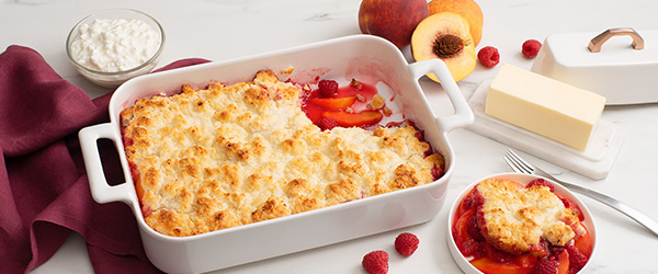 Photo of Peach Raspberry Cottage Cheese Cobbler in a deep dish with an individual portion, cottage cheese and a block of butter surrounding the dish.