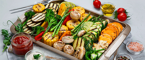 Grilled assorted vegetables in beige tray on light grey background