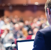 An over-the-shoulder view of a crowd as a presenter stands in front of them with a laptop.