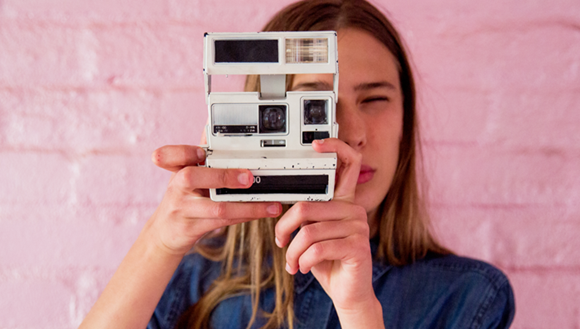 Girl takes a picture with an instant camera
