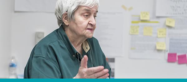 Personne âgée qui donne des commentaires durant une réunion de planification de l'amélioration de la qualité