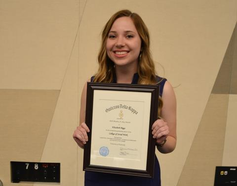 Woman with long, light brown hair smiling and holding award