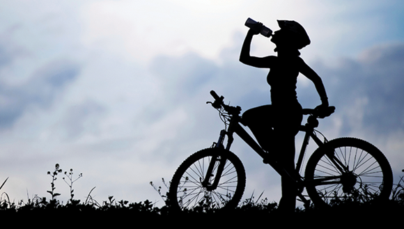 Person having a drink break while riding a bike