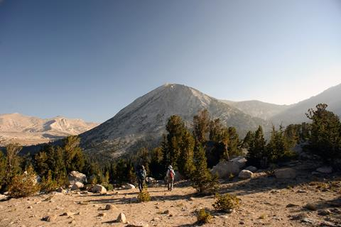 Two hikers appear very small on the trail to Mt. Conness, surrounded by impressive rocky peaks and evergreen trees.
