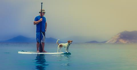 Older man on a paddleboard with his dog