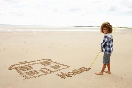 Child standing on a beach. A picture of a house is drawn in the sand.