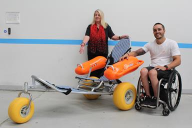 Man pushing a woman into the water in a beach wheelchair