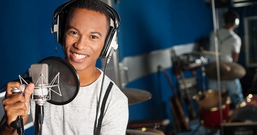 Young disk jockey at microphone in studio