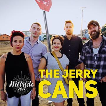 photo of The Jerry Cans taken on the street in Nunavut. The sun is shining and they are standing near a stop sign. There are two women and three men in the photo, dressed in casual millennial clothing. They are smiling.