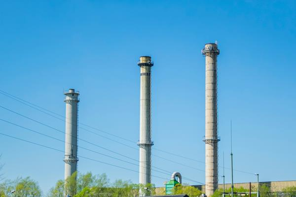 Three tall chimneys that have electric wires passing between the, against a background of a blue sky and greenery.