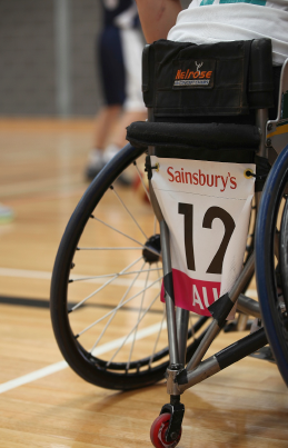 Back of a child's sports wheelchair, showing the player number '12'.