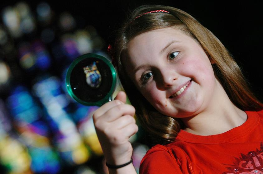 A young girl with brown hair wearing a red t-shirt holding a magnifying glass. In the background there is a stained glass window which is out of focus
