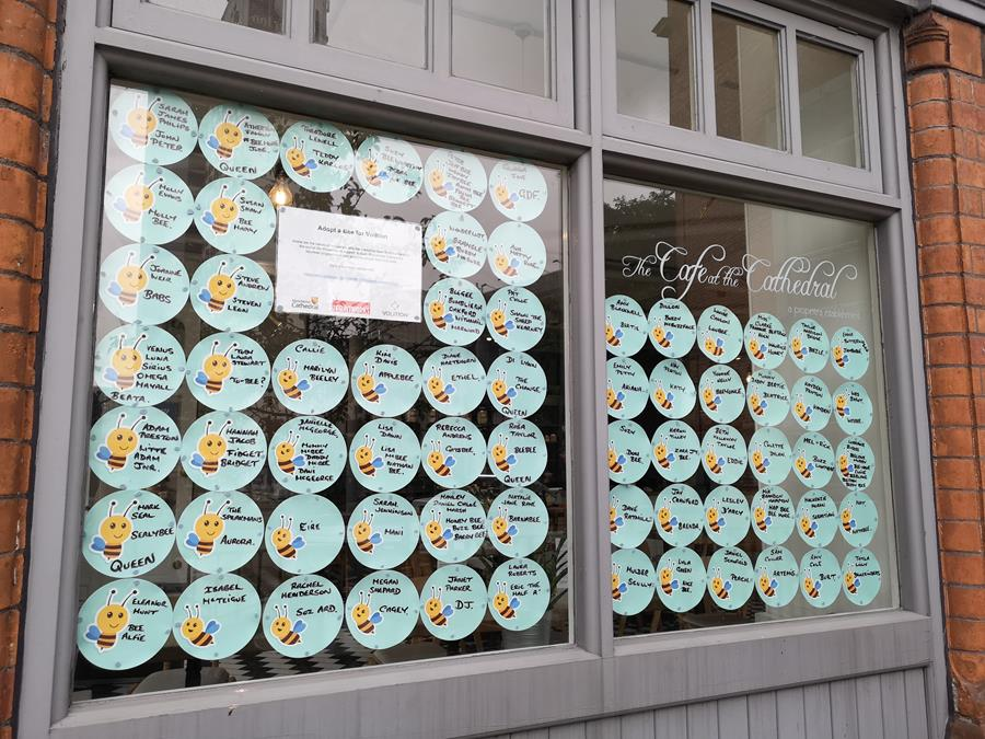 A window with blue stickers containing the name of people who have sponsored a bee