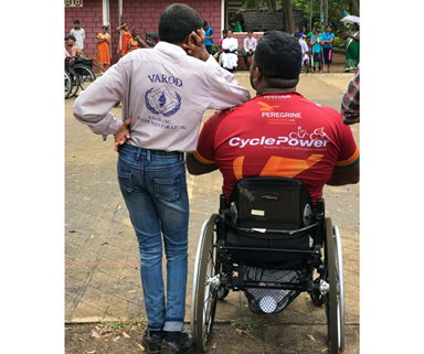 A boy standing next to a man in a wheelchair