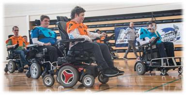 People in electric wheelchairs playing sport in a stadium