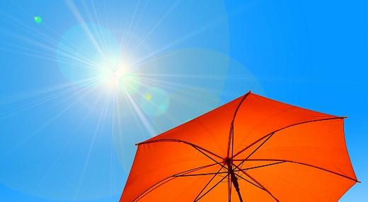 Strong sun shining on open orange umbrella