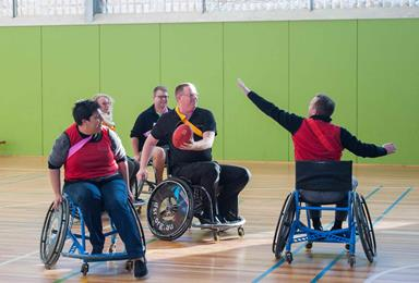 People in wheelchairs playing AFL wheelchair