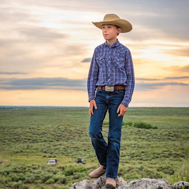A young man in a collared shirt and cowboy hat poses on a rock.