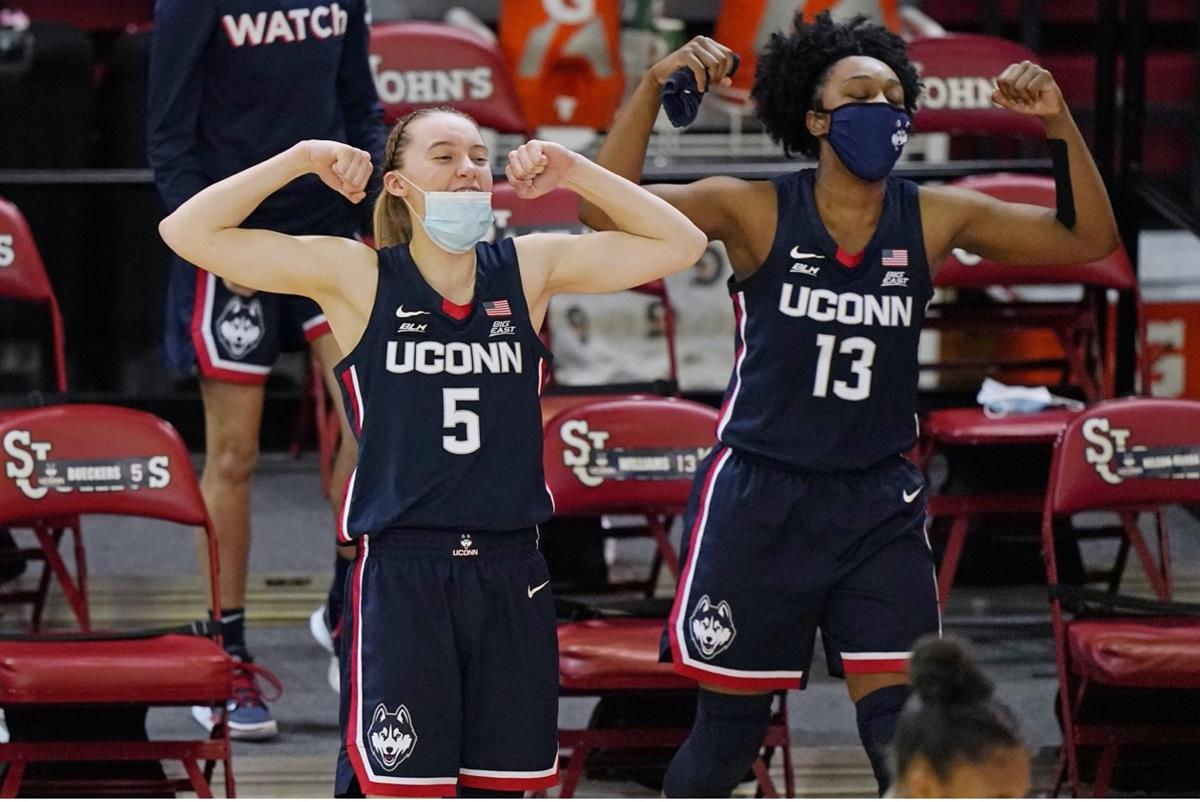 UConn women's basketball team members lifting their arms in strength poses