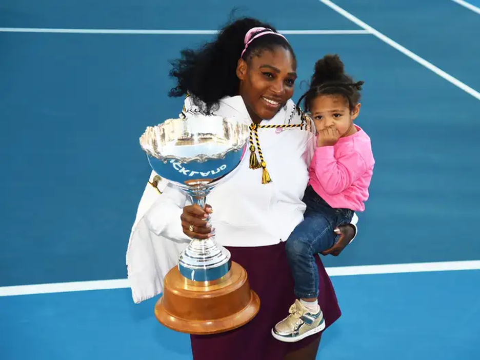 Serena holding trophy in one hand and her daughter, Alexis Olympia Ohanian Jr. in the other while posing for picture on the court