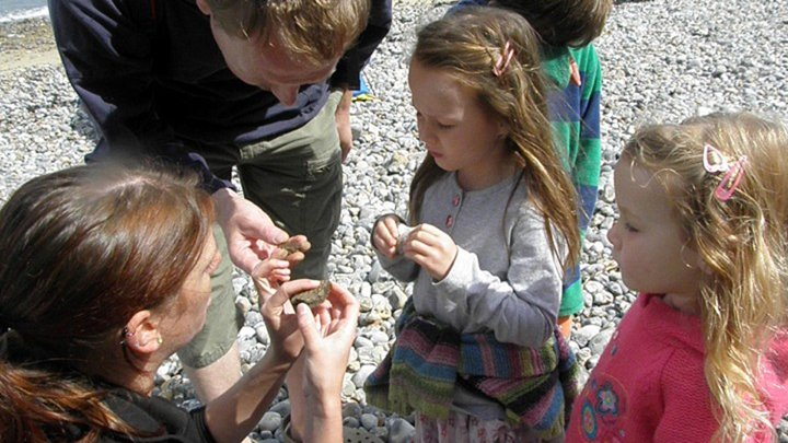 Kids holding fossils and learning