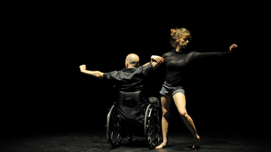 Woman dancer next to Male wheelchair dancer, both are reaching out with one hand while the other hands are intertwined