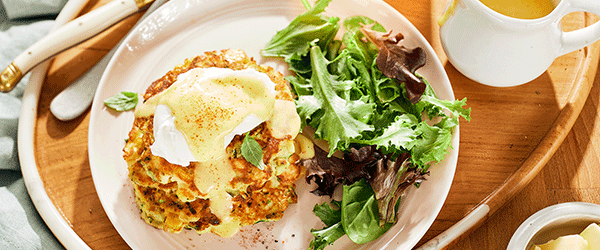 Close up of Zucchini Corn Pancakes plated with a side salad.