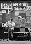 A man plays bottleneck guitar and sings the blues in front of a bar on the streets of London. Photo by Nobuyuki Taguchi.