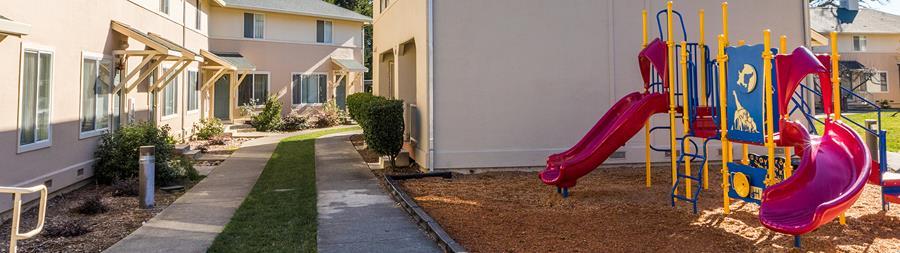 Imagen de un parque infantil, un conjunto de viviendas y una pasarela